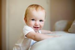 Bebé que se opone contra un sofá Fotografía de archivo libre de regalías
