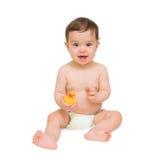 Bebé que se sienta con el pato y la sonrisa Foto de archivo