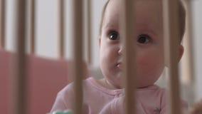 Bebé que se sienta con una cara seria almacen de metraje de vídeo