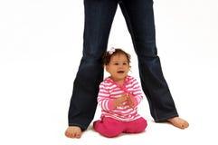 Bebé que se sienta debajo de los lesgs de la mama Foto de archivo