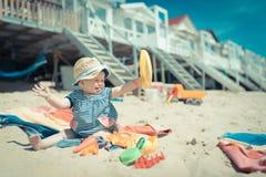 Bebé que se sienta en arena del te en la playa que juega y que ríe Fotos de archivo