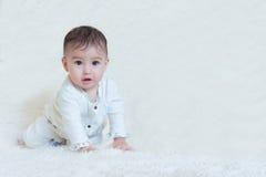 Bebé que se sienta en el fondo blanco Imagen de archivo libre de regalías