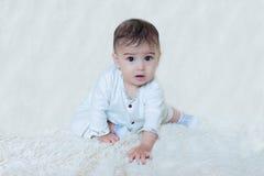 Bebé que se sienta en el fondo blanco Fotografía de archivo