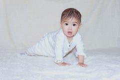 Bebé que se sienta en el fondo blanco Imagenes de archivo