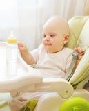 Bebé que se sienta en el hogar de la tabla con la botella plástica Fotos de archivo libres de regalías