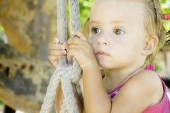 Bebé que se sienta en el oscilación y que mira apagado en la distancia ella tiene ojos muy hermosos fotos de archivo