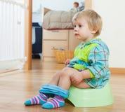 Bebé que se sienta en el potty verde imagenes de archivo