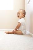 Bebé que se sienta en el suelo Fotos de archivo