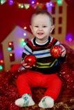 Bebé que se sienta en fondo de una guirnalda de luces y que sostiene bolas de una Navidad del rojo Fotos de archivo libres de regalías