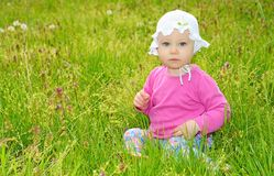 Bebé que se sienta en hierba verde imagen de archivo