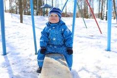 Bebé que se sienta en la oscilación vieja en invierno Imagen de archivo