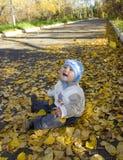 Bebé que se sienta en la tierra Fotografía de archivo