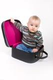 Bebé que se sienta en su maleta Foto de archivo