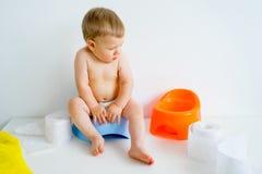 Bebé que se sienta en un potty imagenes de archivo