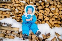 Bebé que se sienta en una pila de leña con una nieve del invierno Imagen de archivo