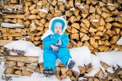Bebé que se sienta en una pila de leña con una nieve del invierno Imagen de archivo libre de regalías