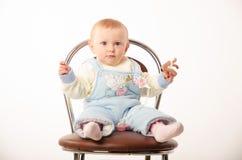 Bebé que se sienta en una silla, estudio Imagen de archivo libre de regalías