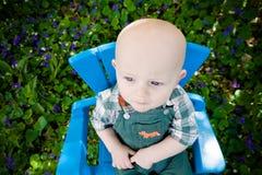 Bebé que se sienta entre las flores Imagenes de archivo