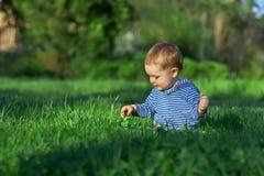 Bebé que senta-se entre a grama verde no gramado da mola Imagem de Stock