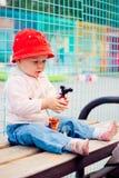 Bebé que senta-se no banco que joga com brinquedo Fotografia de Stock