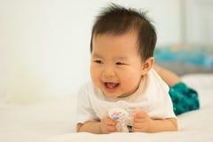 Bebé que sonríe en la cama Fotos de archivo