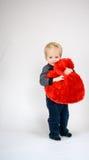 Bebé que sonríe y que abraza un corazón de la felpa Foto de archivo