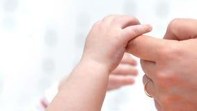 Bebé que sostiene el finger del ` s de la madre almacen de video
