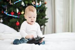 Bebé que sostiene el regulador de RC en el tiempo de la Navidad Imagen de archivo libre de regalías