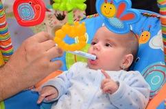 Bebé que toma el jarabe en silla del juego Imagenes de archivo