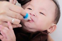 Bebé que toma la medicina con el dropper imagen de archivo libre de regalías