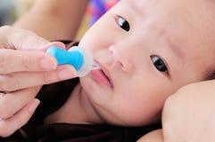 Bebé que toma la medicina con el dropper imagenes de archivo