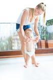 Bebé que toma las primeras medidas con ayuda de las madres Imagenes de archivo