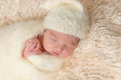 Bebé que toma una siesta presionando sus manos para hacer frente, primer Foto de archivo libre de regalías