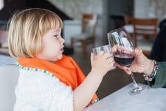 Bebé que tuesta el vidrio de agua con la taza del vino Imagen de archivo