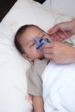 Bebé que usa el espaciador para la infección respiratoria Imagen de archivo