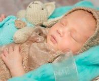 Bebé recién nacido adorable con el conejito-juguete en choza Imagenes de archivo