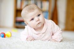Bebé recién nacido adorable que miente en el vientre en el dormitorio o el cuarto de niños soleado blanco Fotografía de archivo libre de regalías
