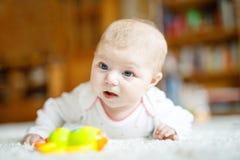Bebé recién nacido adorable que miente en el vientre en el dormitorio o el cuarto de niños soleado blanco Foto de archivo libre de regalías