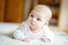 Bebé recién nacido adorable que miente en el vientre en el dormitorio o el cuarto de niños soleado blanco Fotos de archivo