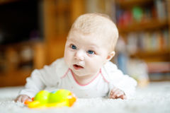 Bebé recién nacido adorable que miente en el vientre en el dormitorio o el cuarto de niños soleado blanco Imagen de archivo