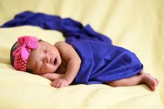 Bebé recién nacido asiático en el fondo amarillo envuelto con el paño azul fotos de archivo