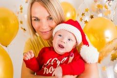Bebé recién nacido con la mamá en el fondo de las bolas de la Navidad Fotos de archivo