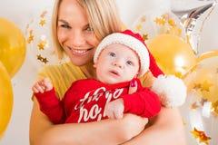 Bebé recién nacido con la mamá en el fondo de las bolas de la Navidad Foto de archivo