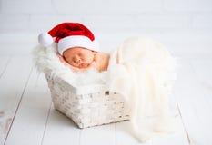 Bebé recién nacido del durmiente en el casquillo de Papá Noel de la Navidad Imagen de archivo