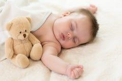 Bebé recién nacido durmiente con el oso de peluche imagen de archivo