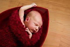 Bebé recién nacido durmiente en capullo rojo Imagen de archivo