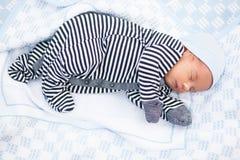 Bebé recién nacido durmiente en mameluco rayado en la sobrecama fotografía de archivo
