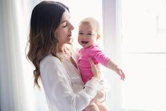 Bebé recién nacido en la mano de su madre en la ventana imágenes de archivo libres de regalías