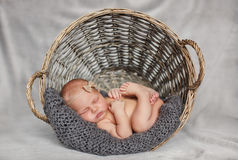 Bebé recién nacido en una cesta de mimbre redonda imagenes de archivo