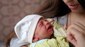 Bebé recién nacido gritador dulce en la mamá en las manos Bebé gritador recién nacido Grito de los niños almacen de metraje de vídeo